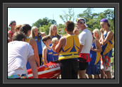 Image of Ryan standing over boat talking to some of the Pisiquid Canoe Club athletes