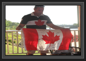 Image of Ryan presenting the Pisiquid Canoe Club with a Canadian flag with the Canoe/Kayak Canada Olympic athletes signatures on it