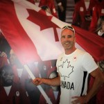 Ryan holding the Canadian flag with Olympic ceremonies photo in background (Photo: Doris Corbin)