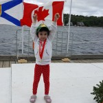 Ryan's daughter Layla holding daddy's medal and standing on podium